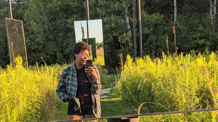 The author standing in a field surrounded by mirrors.